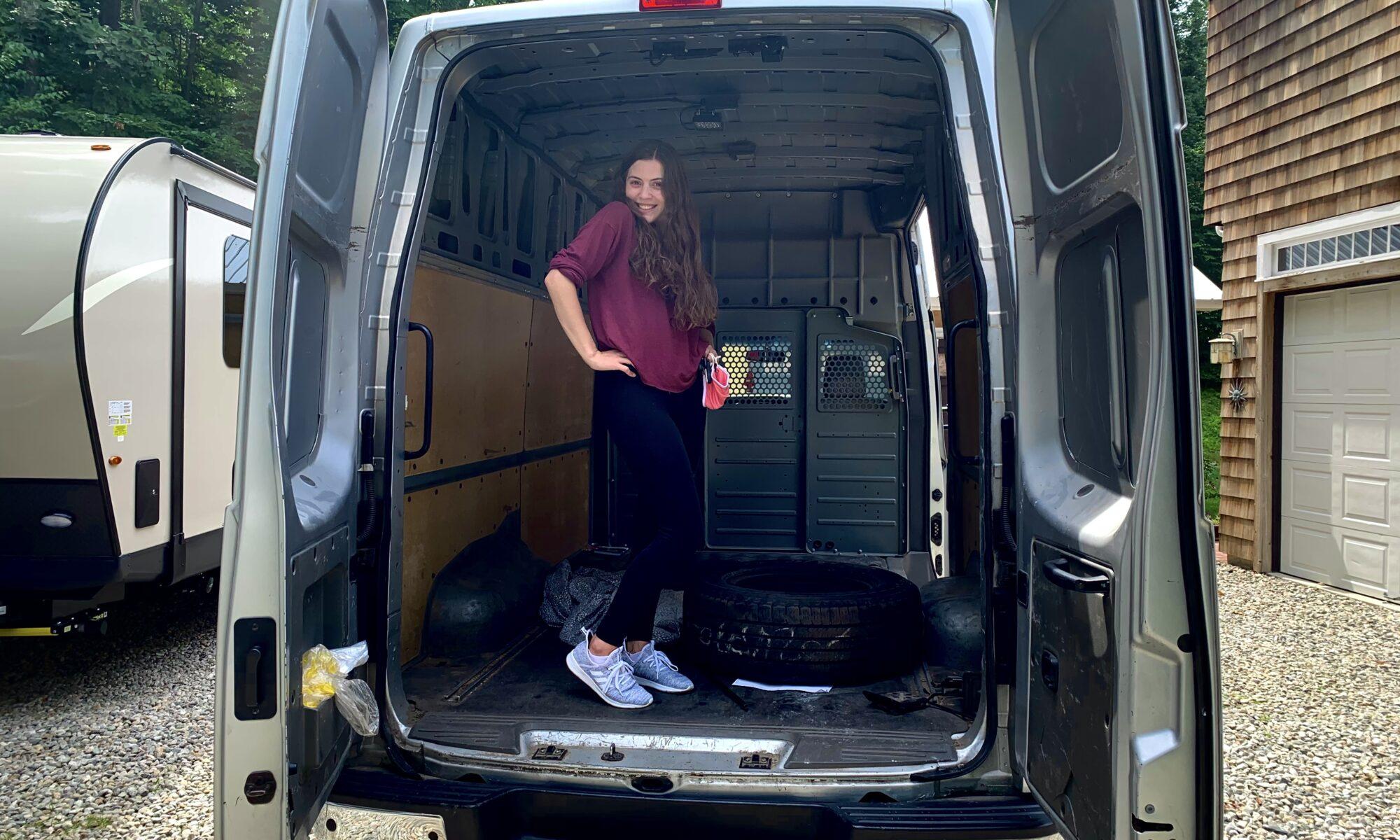 Woman standing in back of opened Camper Van