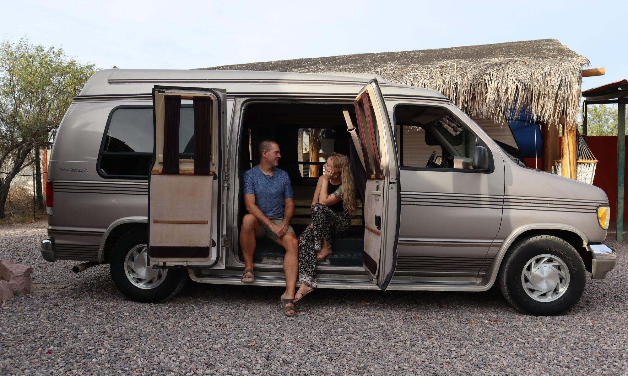 Couple sits in side door of camper van