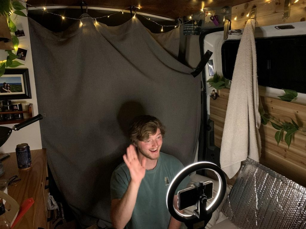 vanlifer working remotely in front of camera and ring light