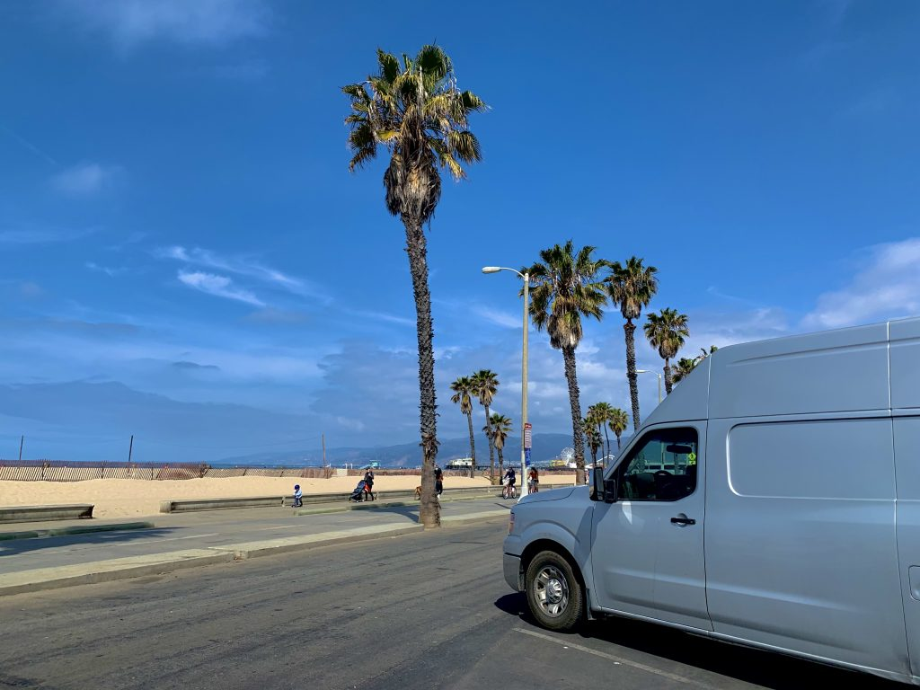 van parked by beach and palm trees in free campsites