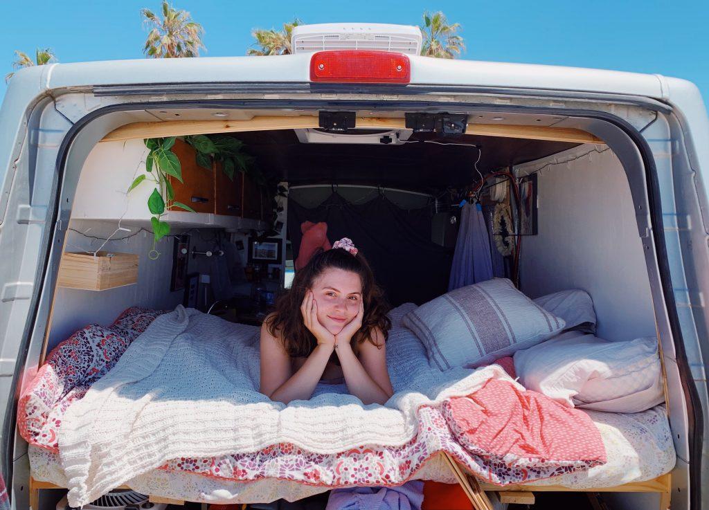 woman sitting in back of camper van