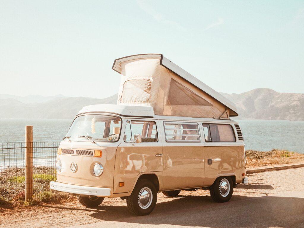 Beige Volkswagen van with pop up camper top parked along coast