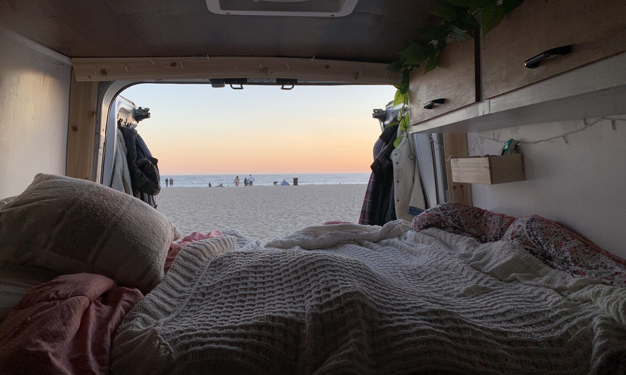 Inside a van looking onto a sandy beach and ocean at sunset