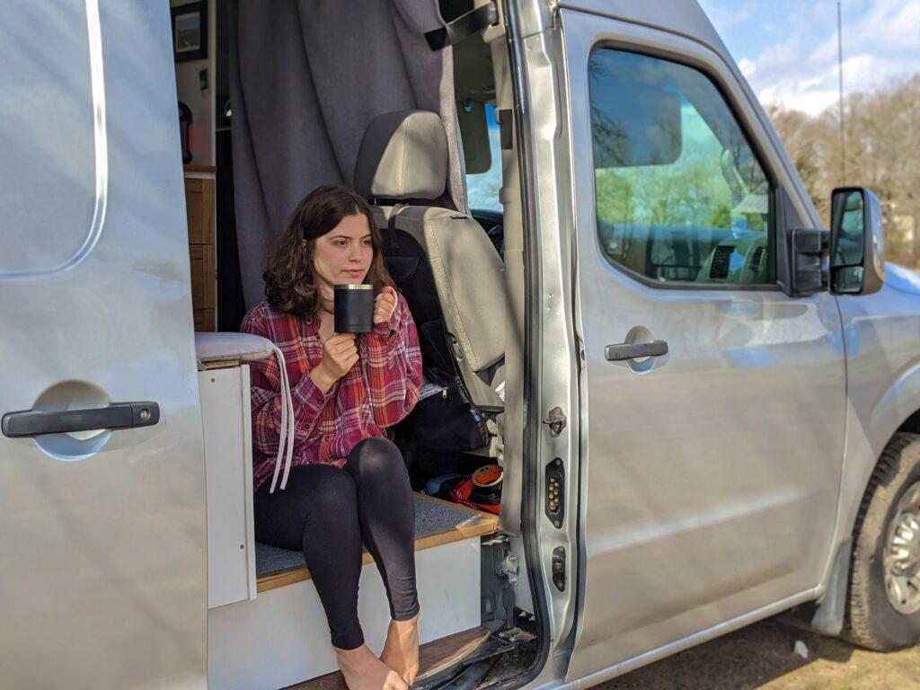 Woman sitting in doorway of van drinking from a mug.