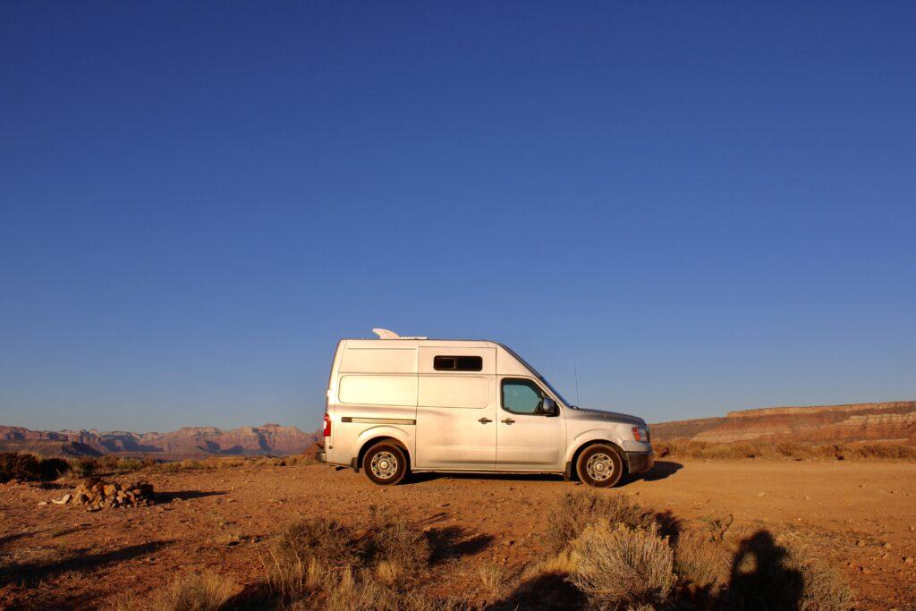 Nissan NV 2500 van parked in desert with blue sky