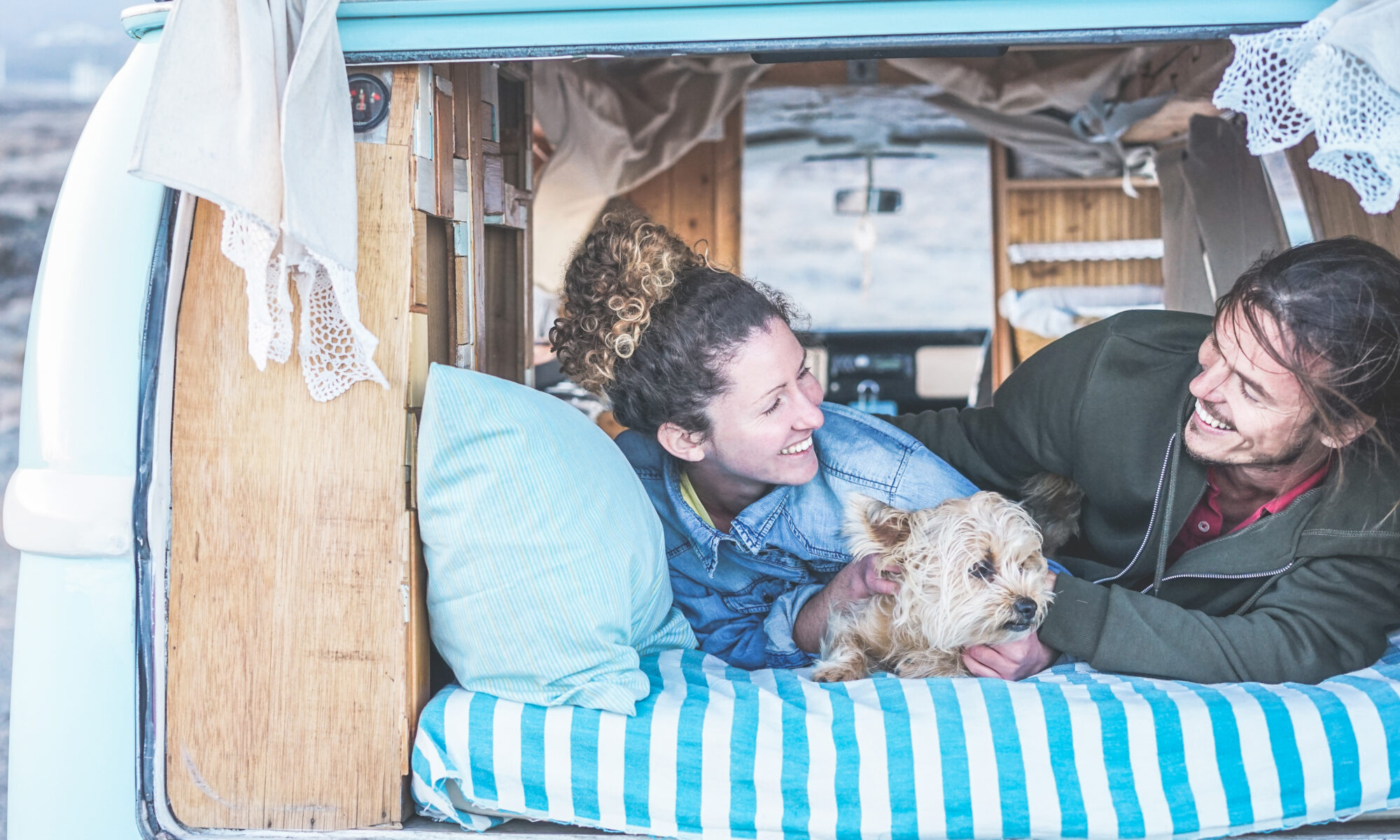 smiling couple laying in back of van conversion with dog