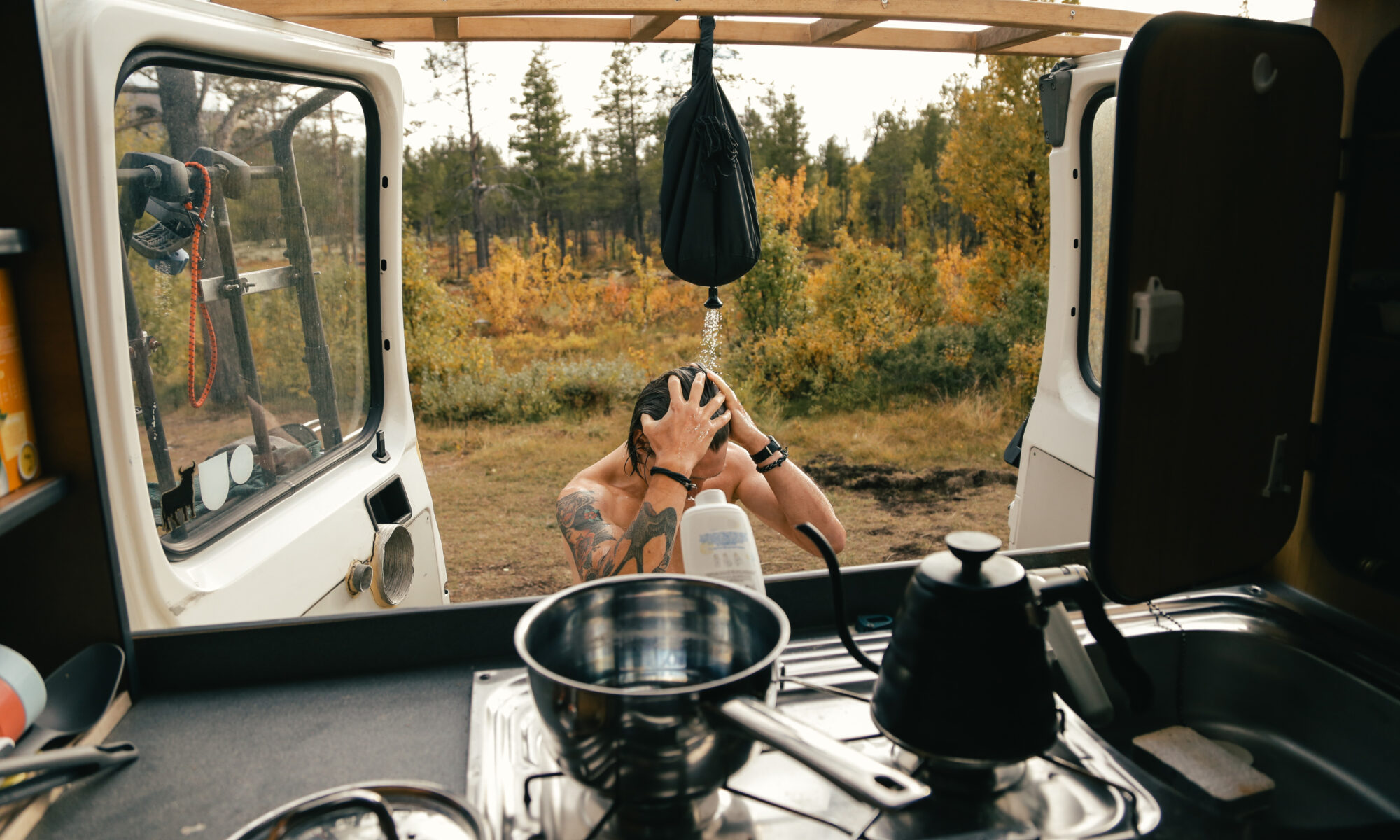 View from inside camper van on young hipster man take shower outdoors from portable shower.