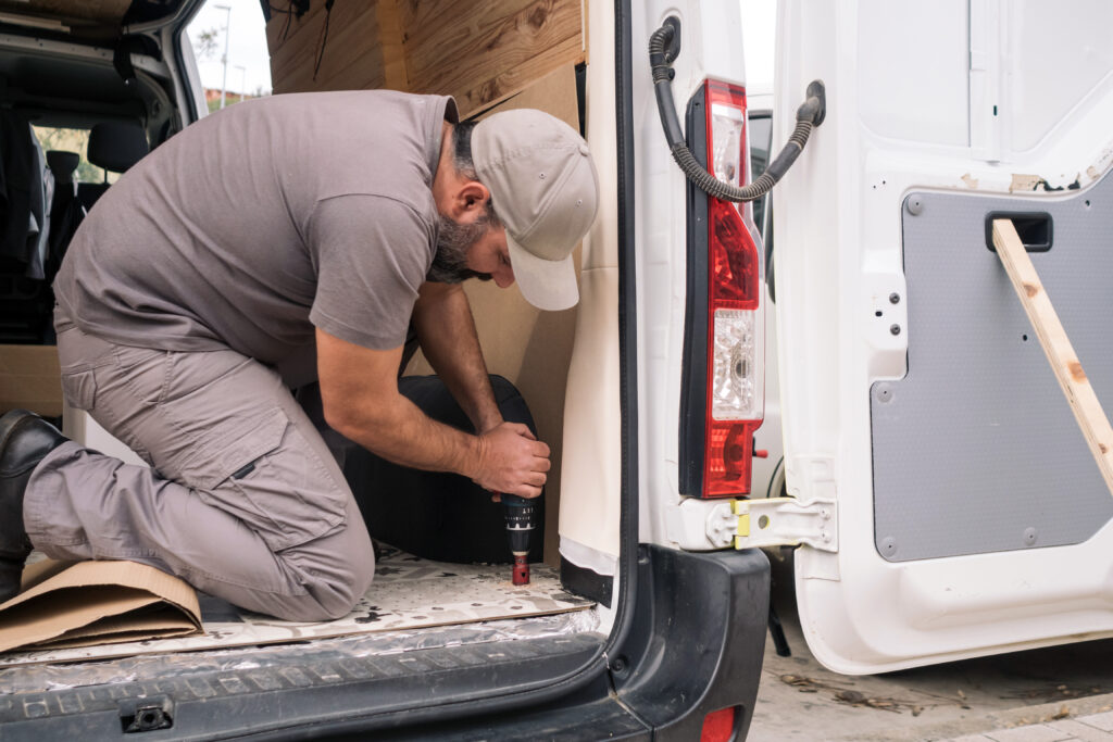 Man drilling a hole in a campervan buildout.