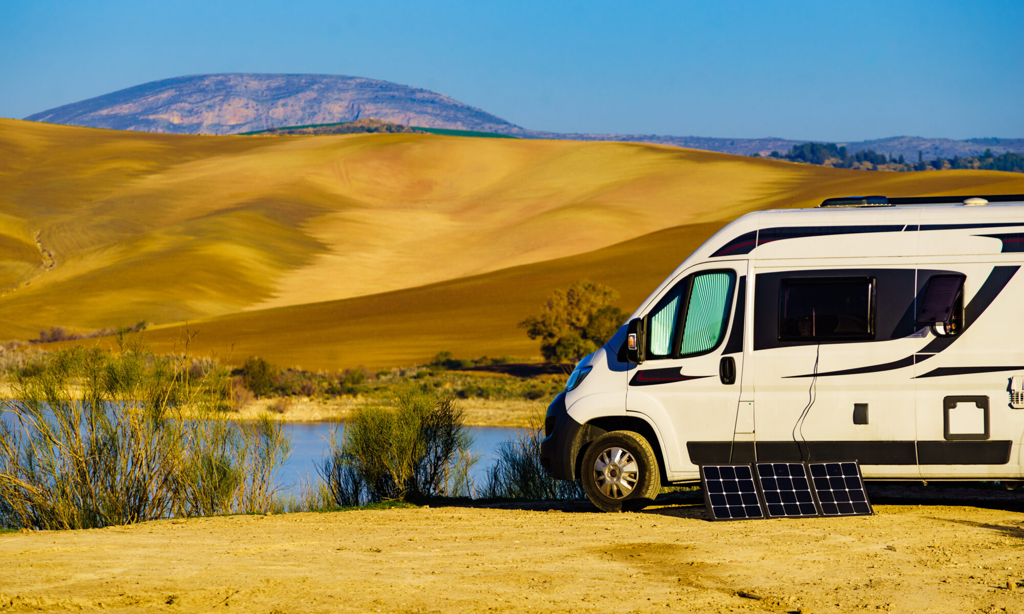 White van with solar panels parked beside a lake