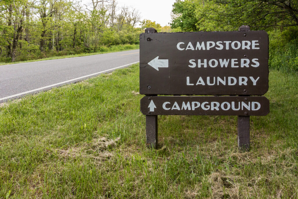 A sign points camp visitors to the store, laundry and shower facilities, and camp sites