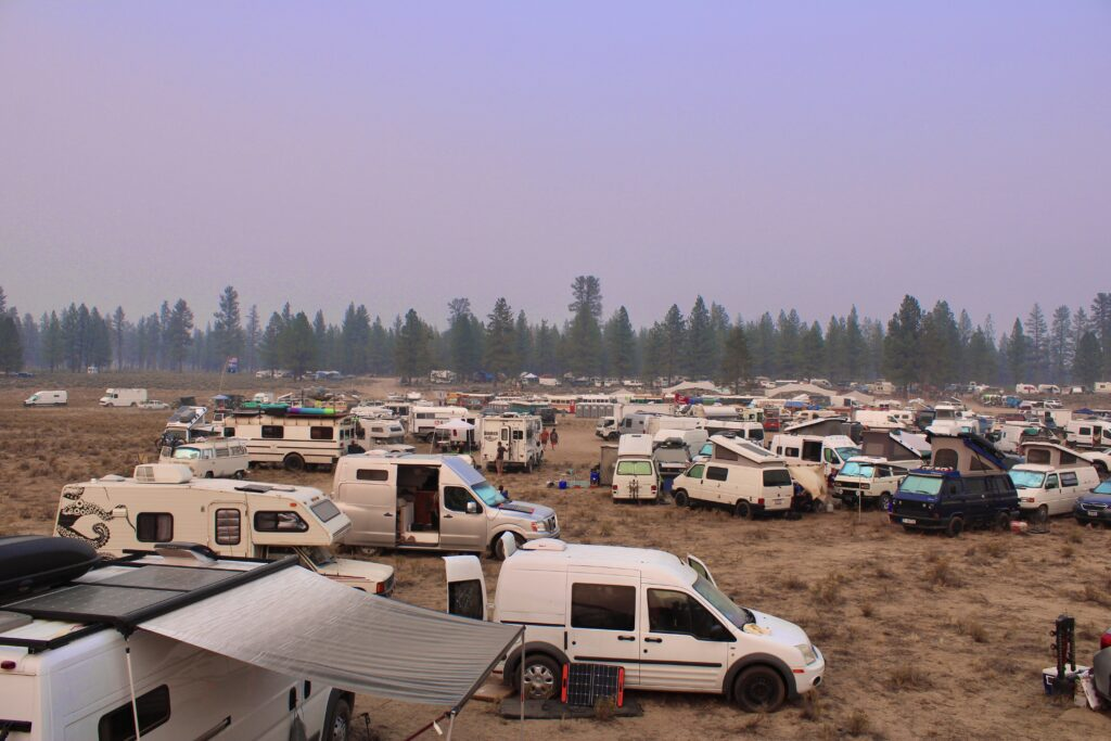 A group of vans and RVs gathered together at a van life meetup in the Oregon outback with pine trees and a sunset in the distance.