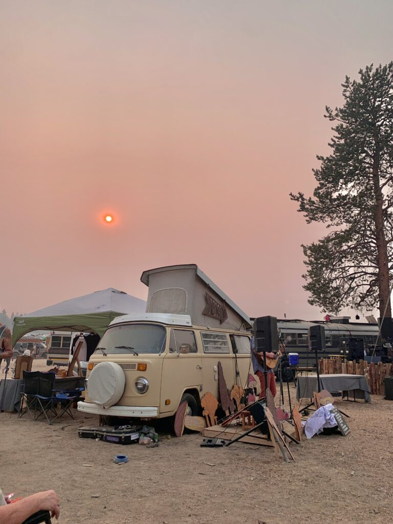 A tan vanagon with a small stage set in front of it and a sunset in the background.