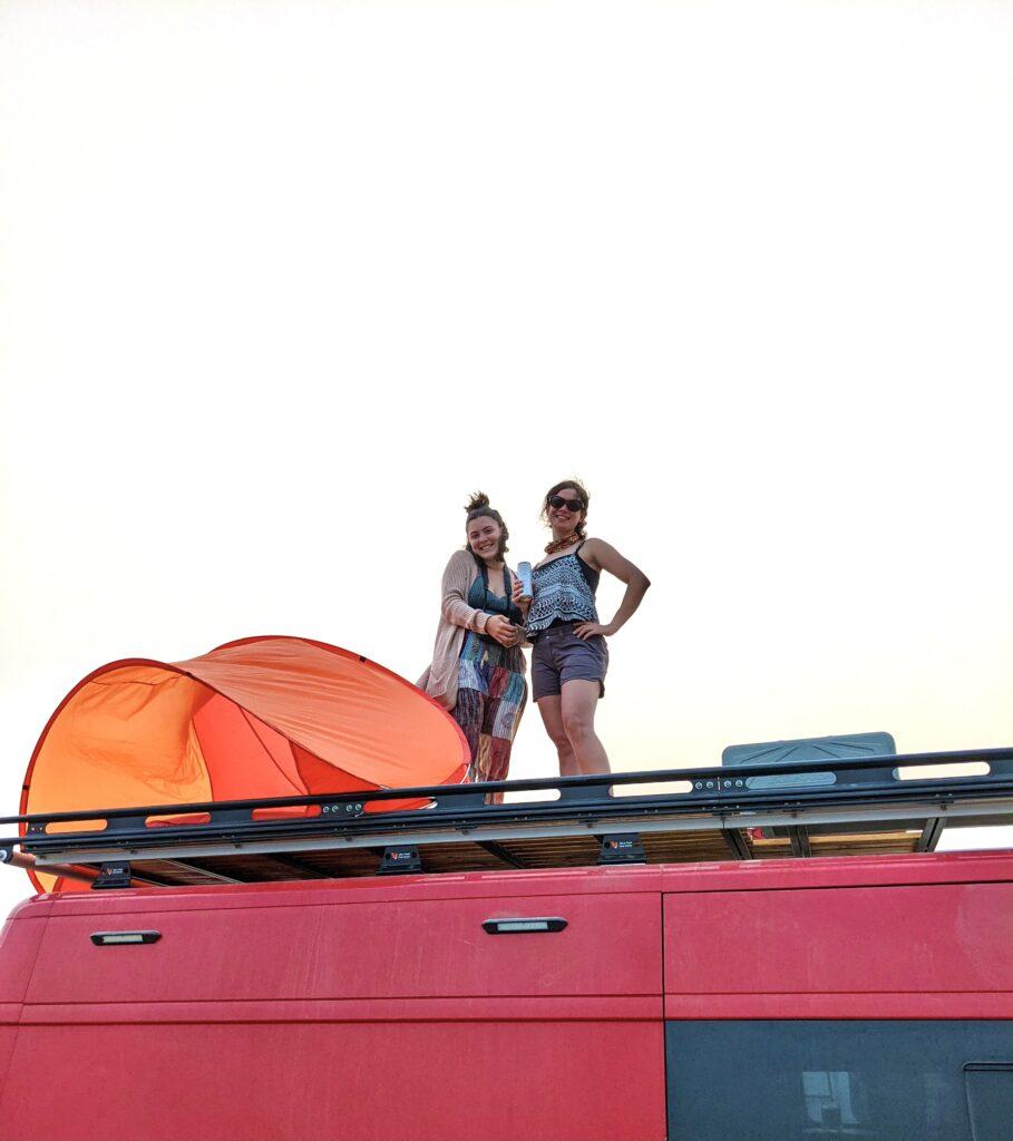 Two girls pose on top of a DIY van rooftop deck.