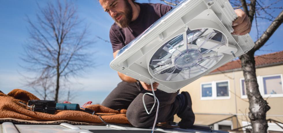 Man installing a van roof fan